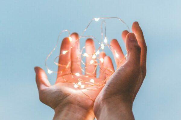 A pair of hands holding a light.