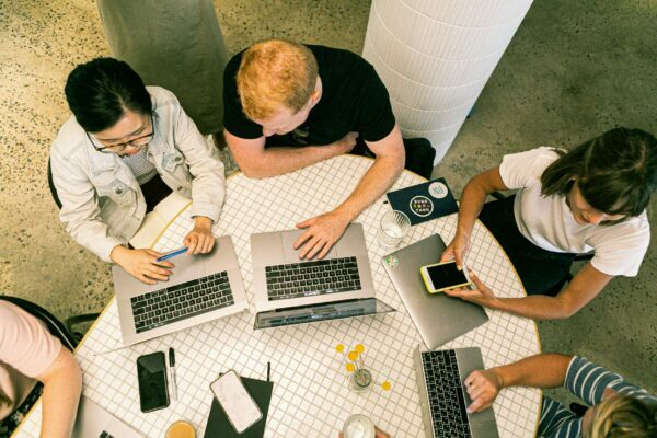 A group of people are sat at a table with their laptops working.