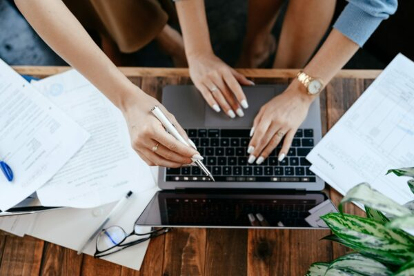 Three hands are touching a laptop keyboard.
