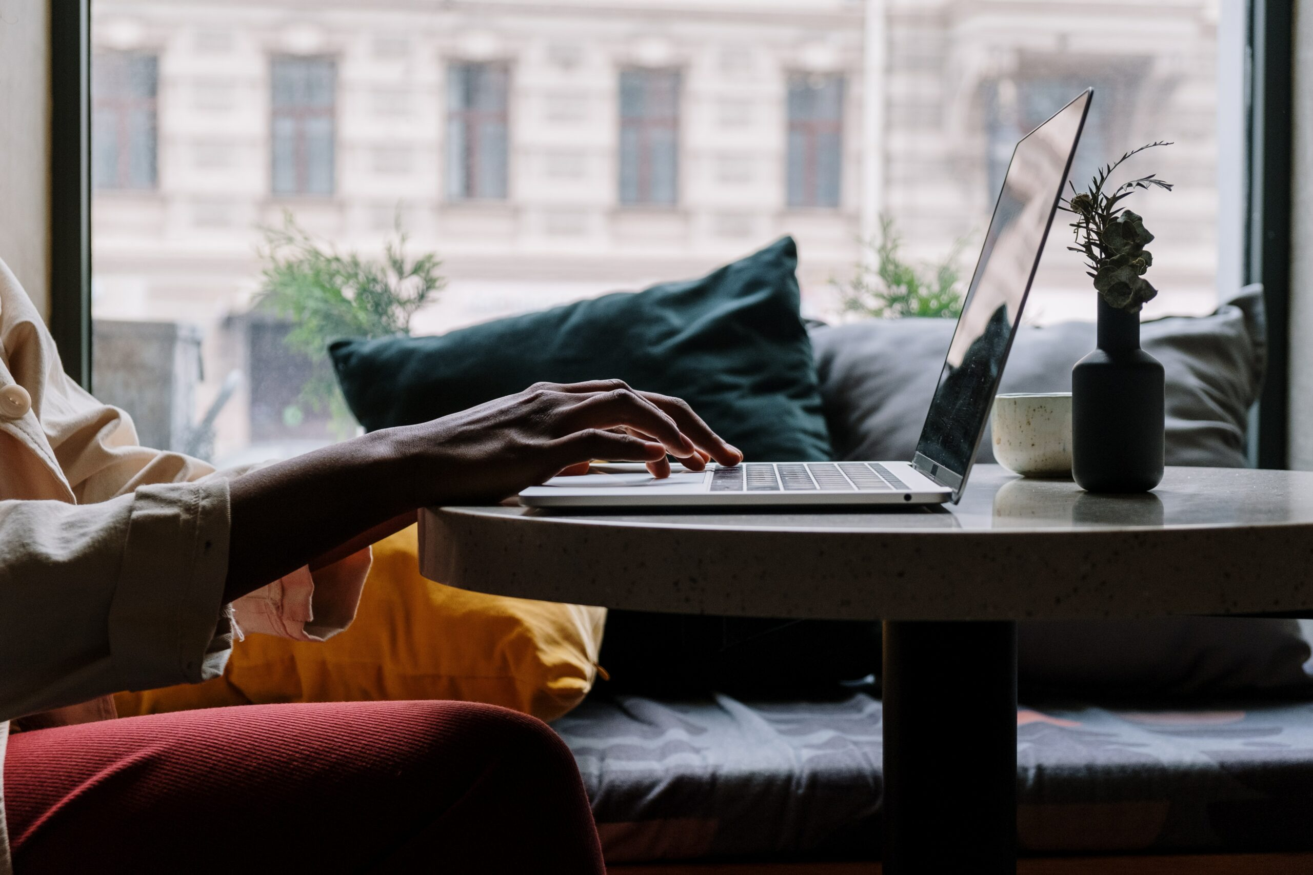 Person sat on sofa using laptop